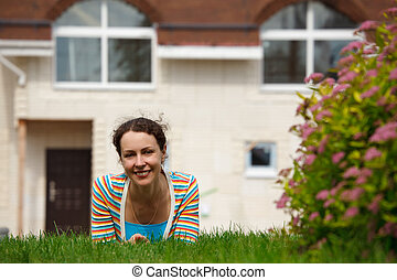 Happy girl on lawn in front of new home. Smiling, she looks into camera. Horizontal format.