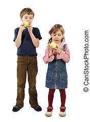 little boy and girl standing and eating big apples isolated on white