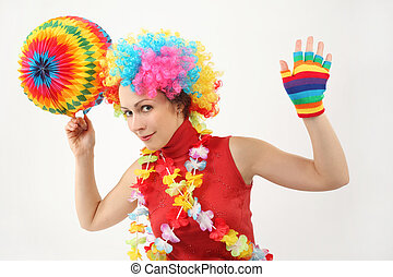 young beauty woman in clown wig, flower garland and multicolored decorative ball, looking at camera, half body
