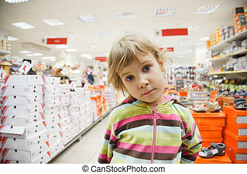 little girl in supermarket alone, chooses in department footwear