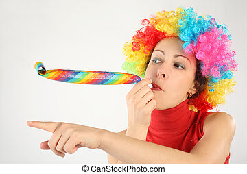 young beauty woman in clown wig and party blower pointing left, half body