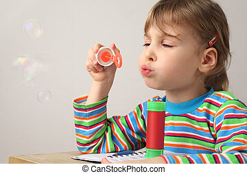 little caucasian girl in multicolored shirt blowing soap bubbles on white background
