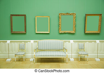 picture frames in green room of museum, stripes chair and sofa with golden wood