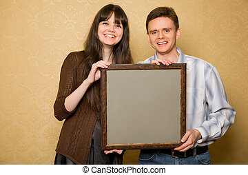 young beautiful woman and smiling man with picture in frame in hands