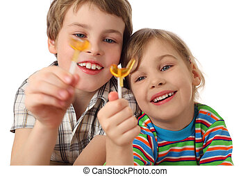 little boy and girl holding lollipops ,looking on it and laughing, half body, isolated on white
