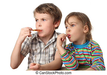 little boy and girl eating lollipops and looking at left side, half body, isolated on white