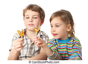 little boy and girl holding lollipops and looking on it, half body, isolated on white