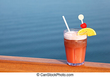 cocktail with fruits in glass on ship deck rail, sea on background, horizontal
