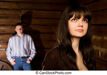 beautiful young woman brunette and young man in wooden log hut, woman standing near wall on background, focus on woman