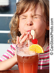 little girl in shirt with pink stripes drinking cocktail with fruits, eyes closed