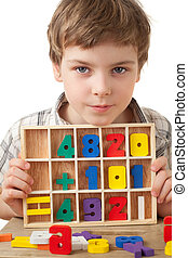 boy in checkered shirt plays in wooden figures in form of...