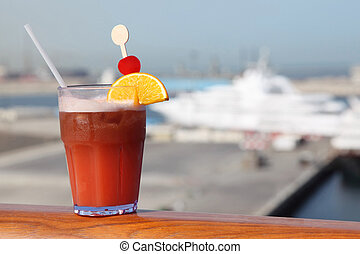 cocktail with fruits in glass on ship deck rail, port with...