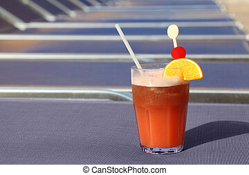 cocktail with fruits in glass on blue beach armchair in cruise liner