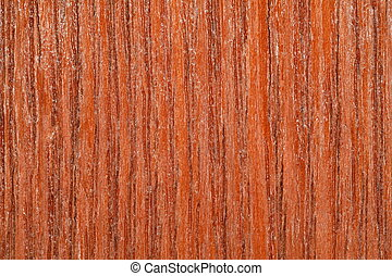 piece of structural wooden board covered with varnish, a brownish-yellow. macro