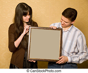 young beautiful woman and smiling man with picture in frame in hands, looking at picture