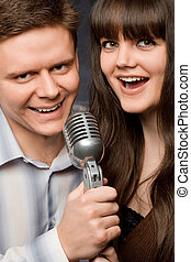 young beautiful woman and smiling man sing in microphone