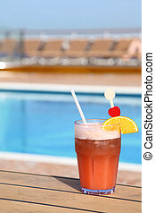 cocktail with fruits in glass on ship deck floor near swimming pool