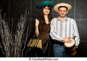 young beautiful woman and smiling man in sombrero and with drum