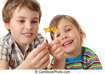 little boy and girl holding lollipops ,looking on it and smiling, half body, isolated on white