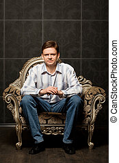 young man sitting in magnificent ancient armchair