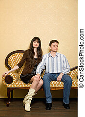 young beautiful woman and man sitting on sofa in room, man...