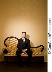 businessman in suit sitting on sofa in room, ?ombined hands together
