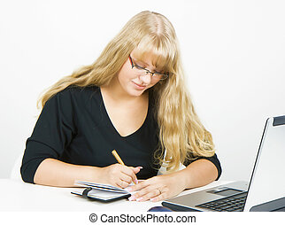 girl with a laptop writes in a notebook