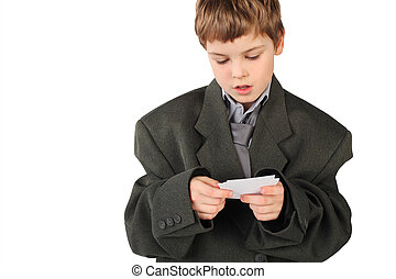 little boy in big grey man's suit looking at  business card isolated on white background