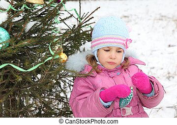 little girl with Christmas-tree decoration in her hands is standing near christmas three
