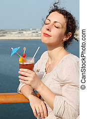 beauty brunette woman in white shirt standing on cruise liner deck and holding cocktail with fruits, eyes closed