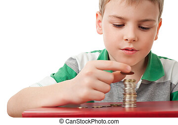 boy in striped T-shirt stacking up coins isolated on white...