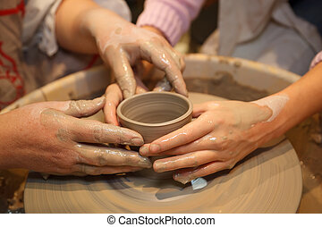 Hands of two people create pot on potter's wheel. Teaching...