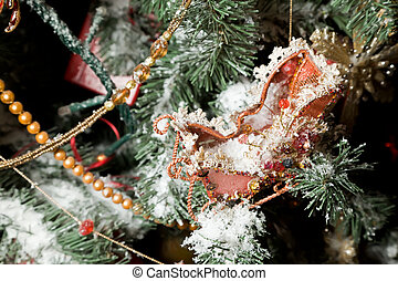 Christmas ornaments in form of sledge on artificial fur-tree, branches in snow
