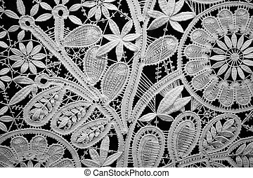 Lace doily on black background, close up. Horizontal format.