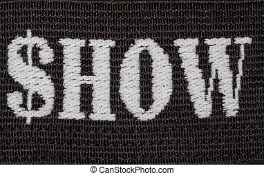 """Word """"show"""" embroidered in white thread on black fabric...."""