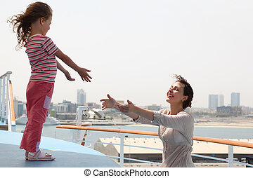 mother and daughter stretching hands to each other, standing on cruise liner deck