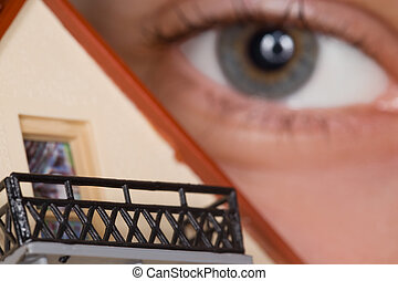 Fragment of face of person near toy plastic house with balcony, Eye close up