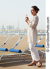 young beauty woman with cocktail standing on cruise liner deck, looking left and smiling