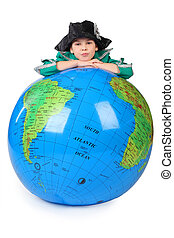 boy in historical dress leans on inflatable globe chin on...