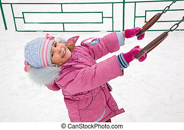 little pretty smiling girl in pink jacket on playground in winter