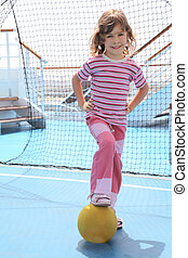 little girl with yellow ball standing near football goal on cruise liner deck, summer day
