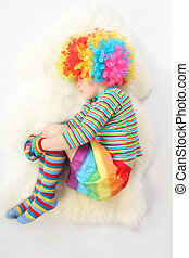 boy in clown dress sleeping view frome above on white background