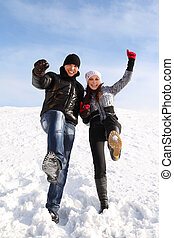 young man and girl stand on snowy area and put one leg up, looking at camera