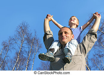 senior with child on shoulders in front of spring birch tree...