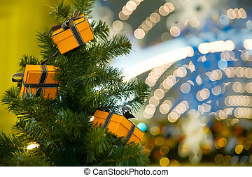 Three celebratory gifts in yellow boxes hanging on Christmas fur-tree