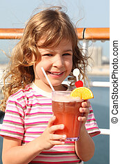 little girl in shirt with pink stripes holding cocktail with fruits, smiling and looking at camera