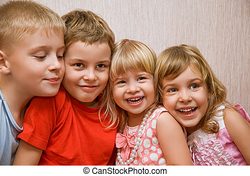 Laughing children four together in cosy room, two pretty girls and two boys