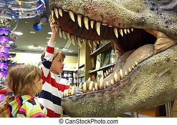 little boy and girl looking in tyrannosaurus opened mouth...