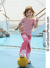 little girl with yellow ball standing near football goal on cruise liner deck and making thumbsup gesture, summer day