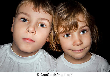 boy and little girl in white T-shirts isolated on black background